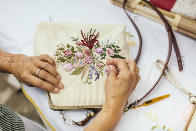 Woman stitching floral design on a purse