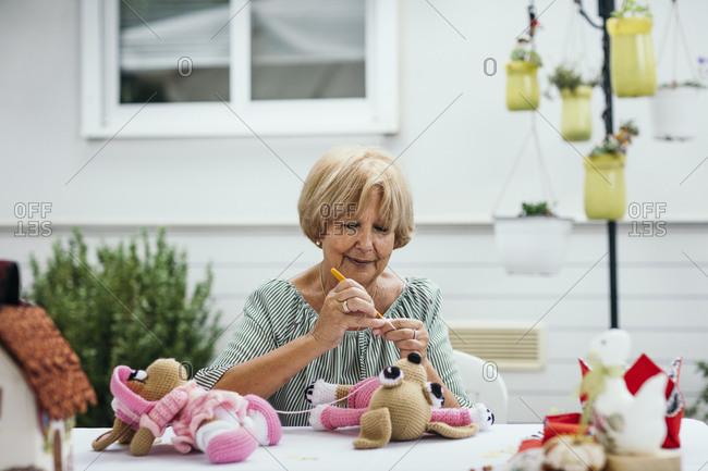 Senior woman crocheting stuffed toys outdoors