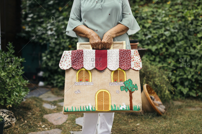 Woman holding house shaped craft bag outdoors