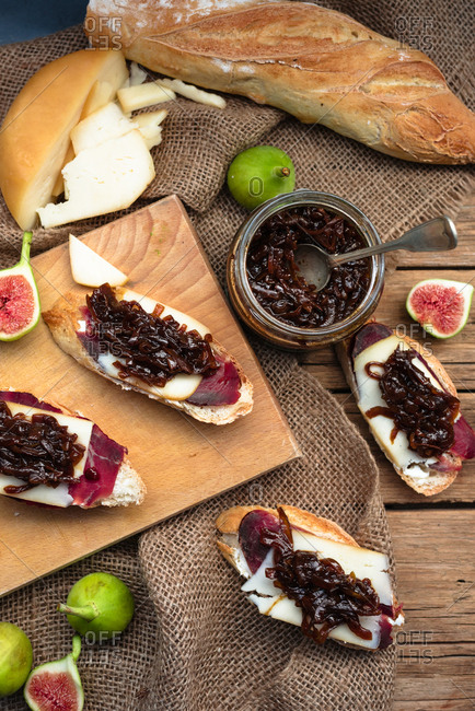 Slices of bread with ham and red onion chutney jam on a wooden background