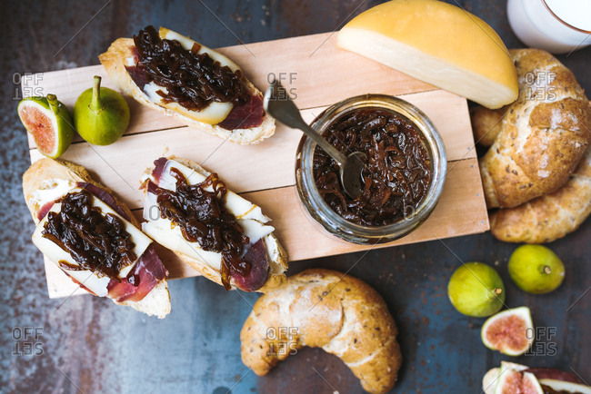 Bread with ham and caramelized red onion jam on a dark background