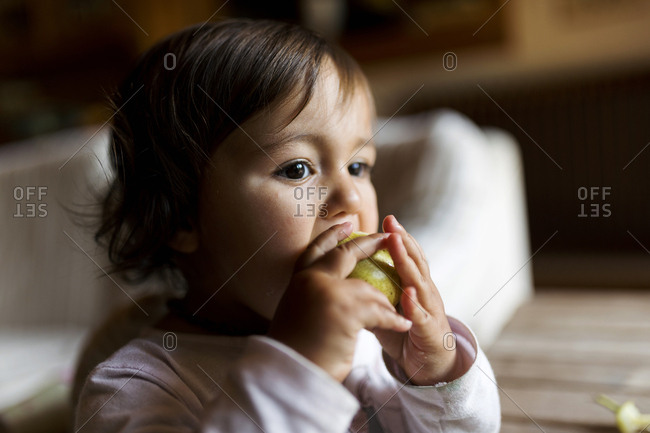 Baby eating a pear