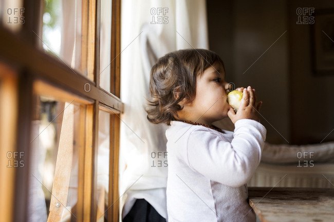 Baby by window eating a pear