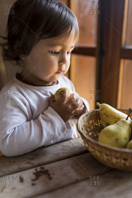 Baby grabbing a pear from a basket