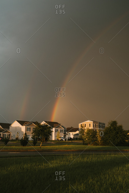 Double rainbow and dark storm clouds above neighborhood