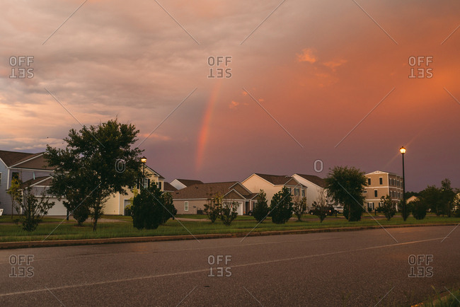 Rainbow and storm clouds above neighborhood at sunset