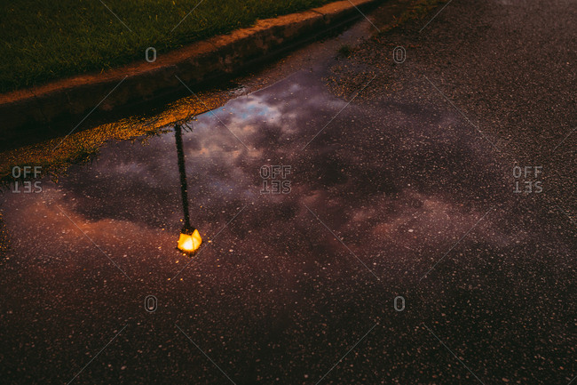 Reflection of streetlamp and cloudy sky in puddle on the side of the road