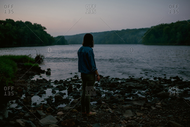 Woman standing on a rocky lakeshore looking out over a lake surrounded by the forest