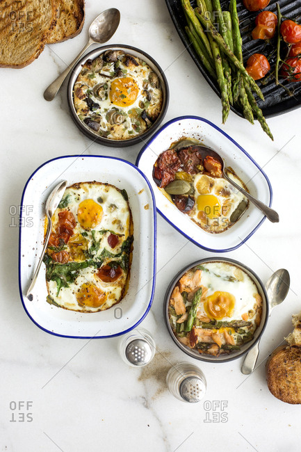 Breakfast dishes of baked eggs and fresh vegetables
