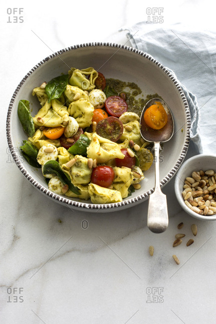 Bowl of pasta with pesto and heirloom tomatoes