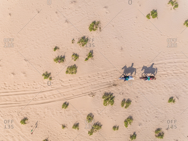Aerial view of two people riding horses in desert, Abu dhabi, UAE.