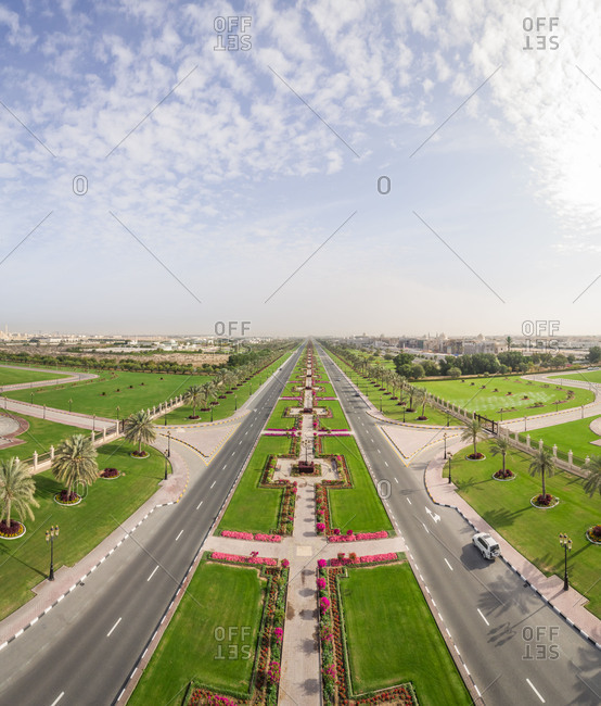 Aerial view of long road and flower beds in University City, Sharjah, UAE.