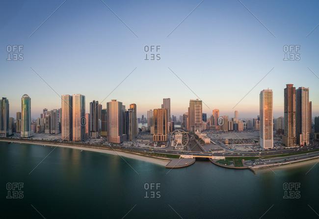 Aerial panoramic view of Ferris wheel and skyscrapers in Dubai, UAE.