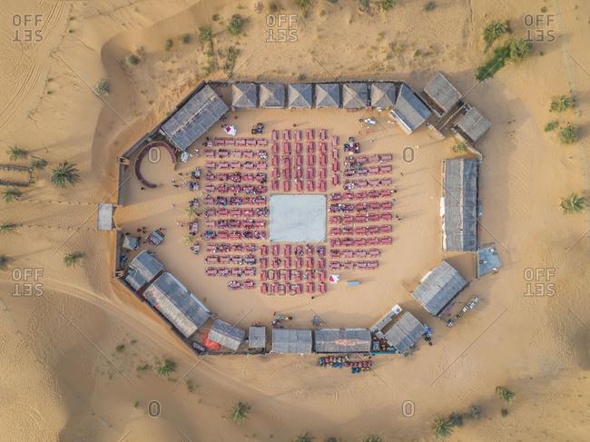 Aerial view of desert safari camp with straw roof huts, Al Awir, Dubai, UAE.