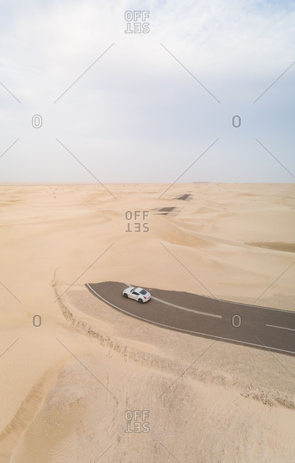 April 7, 2018: Aerial view of white car in road covered by sand in the desert, Abu Dhabi, UAE.