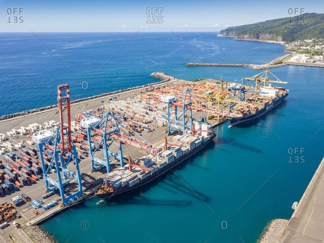 April 11, 2018: Aerial view of cargo ships and shipping containers in Le Port harbor, Reunion island.