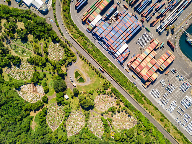 Aerial view of leaf shaped cemetery and shipping containers in harbor, Le Port, Reunion.