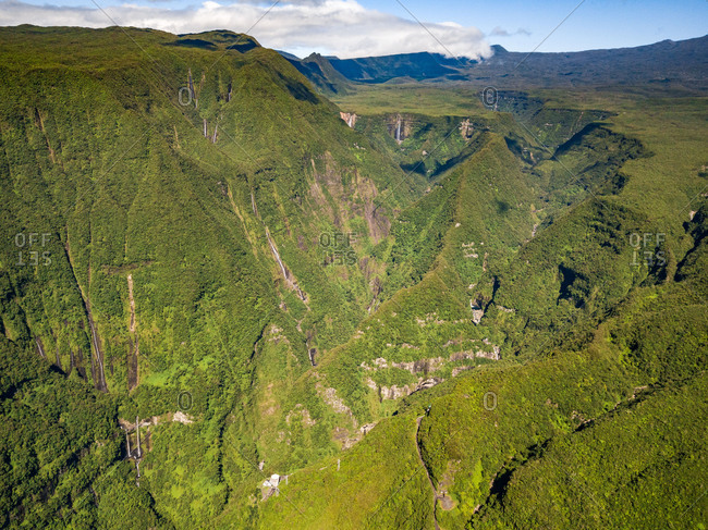 Aerial view of foresty hills and valleys in Foret Departementale du Cratere, Reunion.
