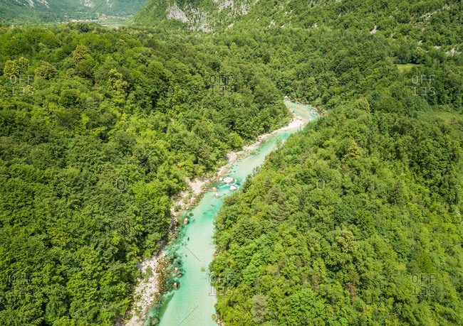 Aerial view of the Soca river surrounded by nature at summer time in Slovenia.