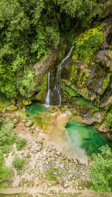 Aerial view of cyclists at Virje waterfall in Soca valley, Slovenia.