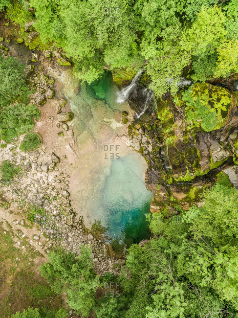 Aerial view of the top of a small waterfall with clean water downhill in Slovenia.