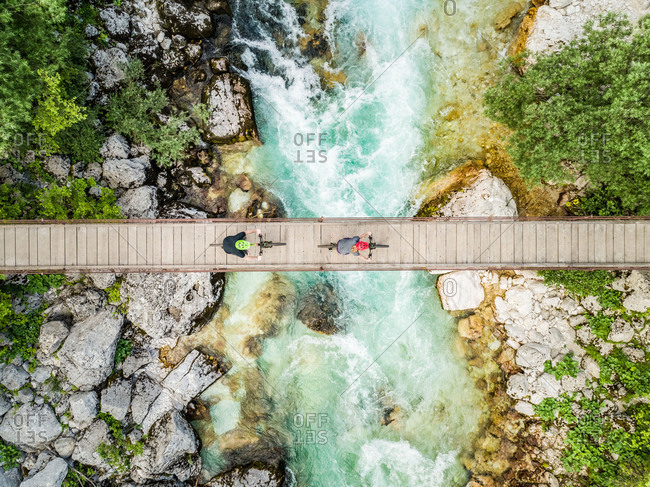 Aerial view of cyclists on wooden suspension bridge on Soca river, Slovenia.