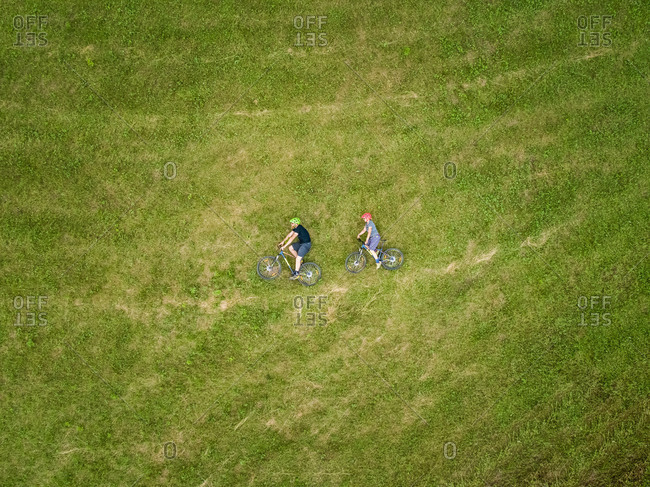 Aerial view of cyclists lying down on the grass with their bicycles in Slovenia.