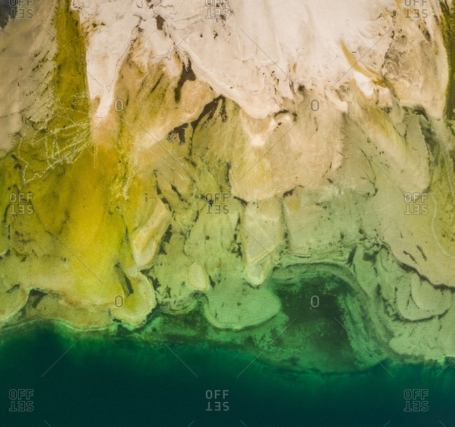 Aerial abstract view of sediment structure and transparent water in Lago del Predil lake, Italy.