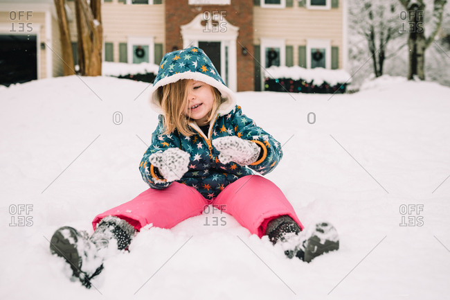 Little girl sitting in snow on a snow day