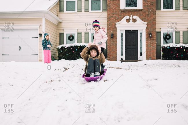 Three kids sledding in their front yard