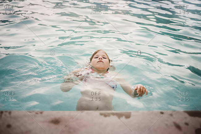 Little girl floating in the pool
