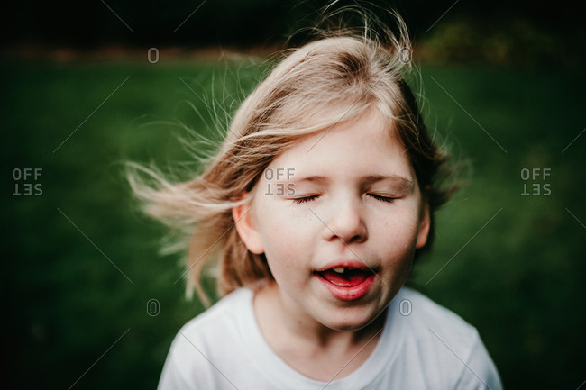 Little girl singing and feeling the breeze stock photo - OFFSET
