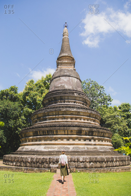 A girl walking towards a Buddhist Temple