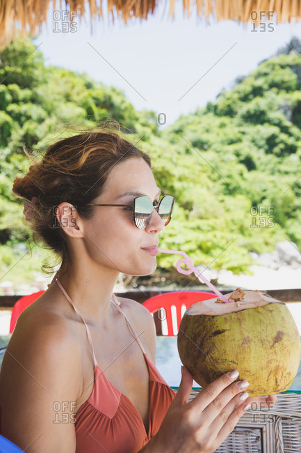 Girl drinking from a coconut on the beach