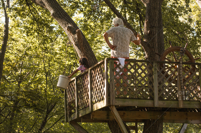 Grandfather in a tree fort with his granddaughter