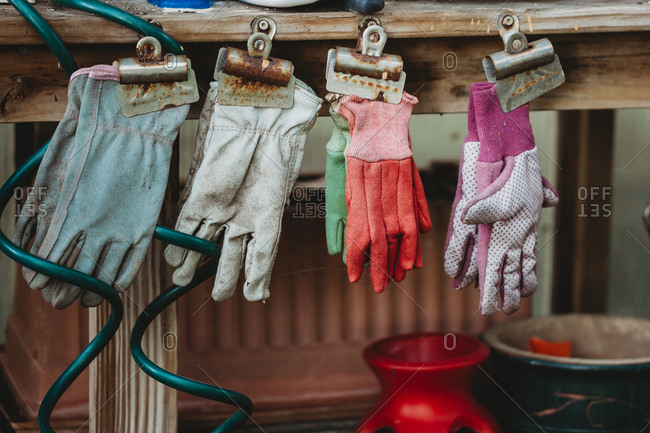 Gardening gloves hanging from rusty clips