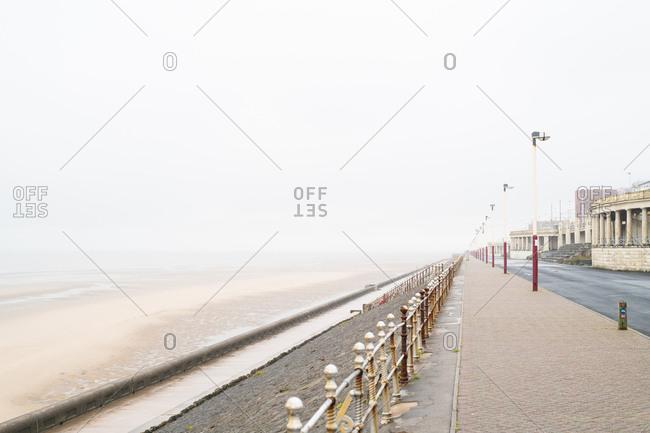 Promenade along sandy beach on a foggy day