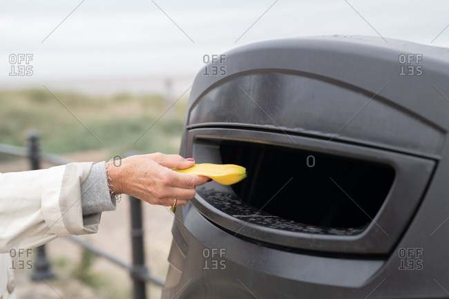 Person putting a banana peel in public outdoor trash can