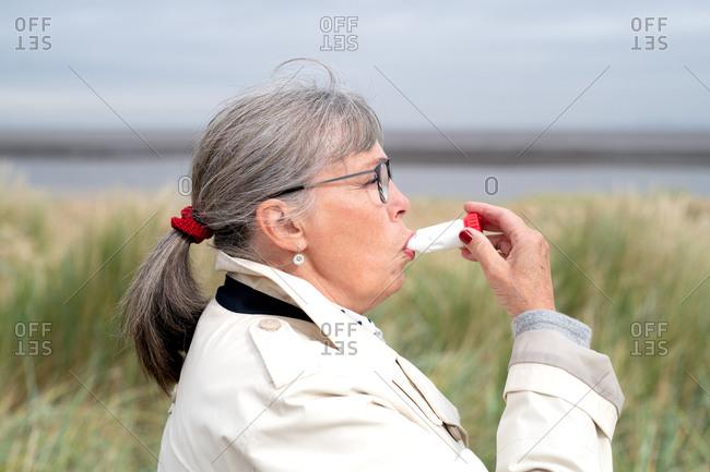 Senior woman using a dry powder inhaler