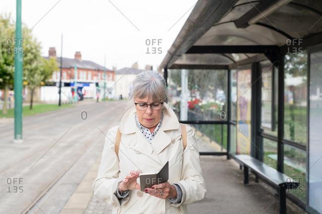 Senior woman using smartphone while waiting at light rail transit station