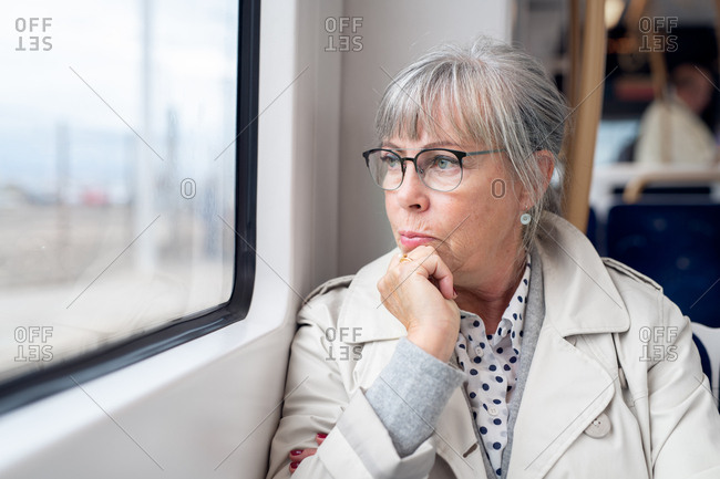 Senior woman sitting on train looking out window
