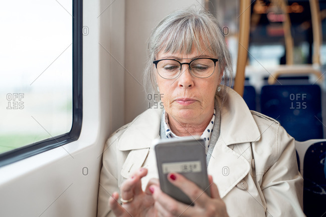 Senior woman sitting on train using her smartphone