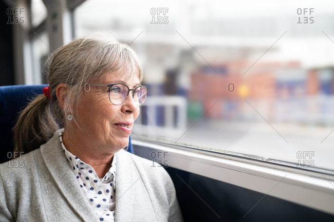 Smiling senior woman looking out window of train