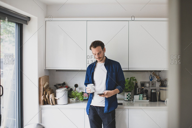 Adult male checking smartphone in kitchen with mug of coffee