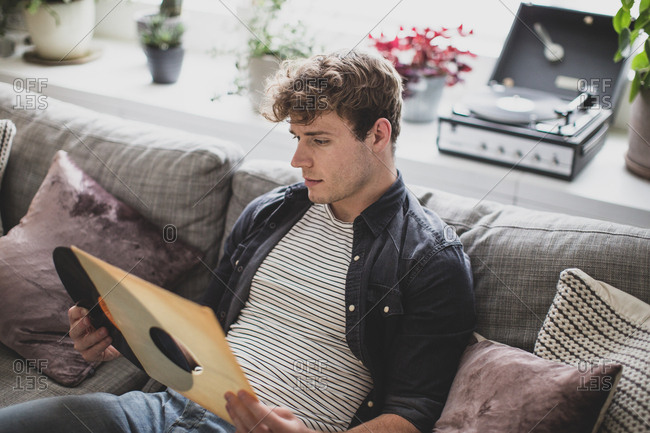 Young adult male looking at vinyl record