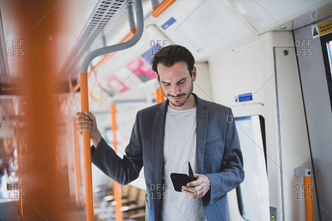 Commuter using smartphone on train
