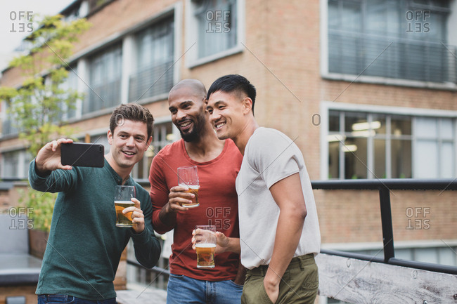 Group of male friends taking a selfie in an outdoor bar
