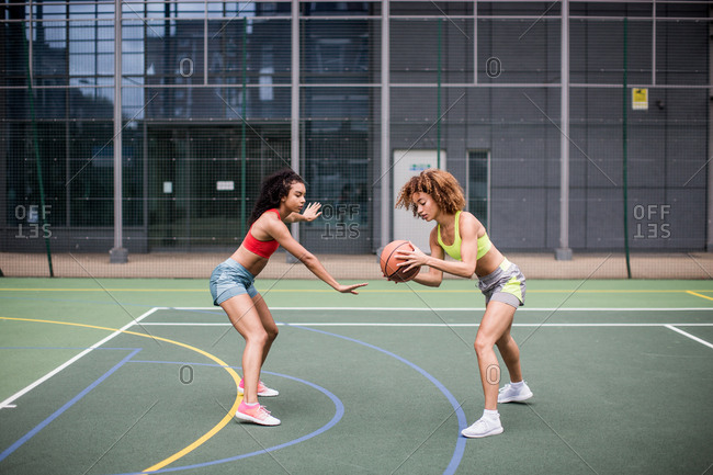 Young adult females playing basketball