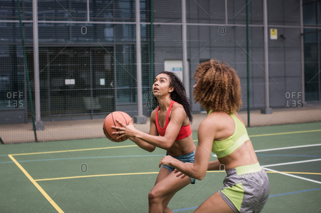 Young adult female basketball player about to shoot a hoop