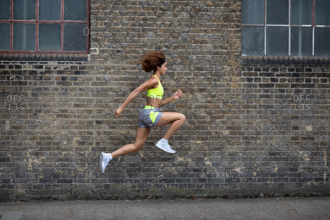 Young adult female leaping in the air with brick wall backdrop